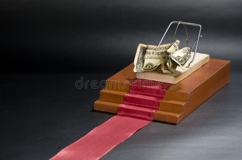 Argent dans une souricière à clapet sur le tapis rouge et le fond noir image stock