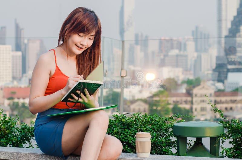 argent de concepts de calculatrice d'affaires La femme asiatique d'affaires sont lisante et writeing des livres Les femmes d'affa images libres de droits