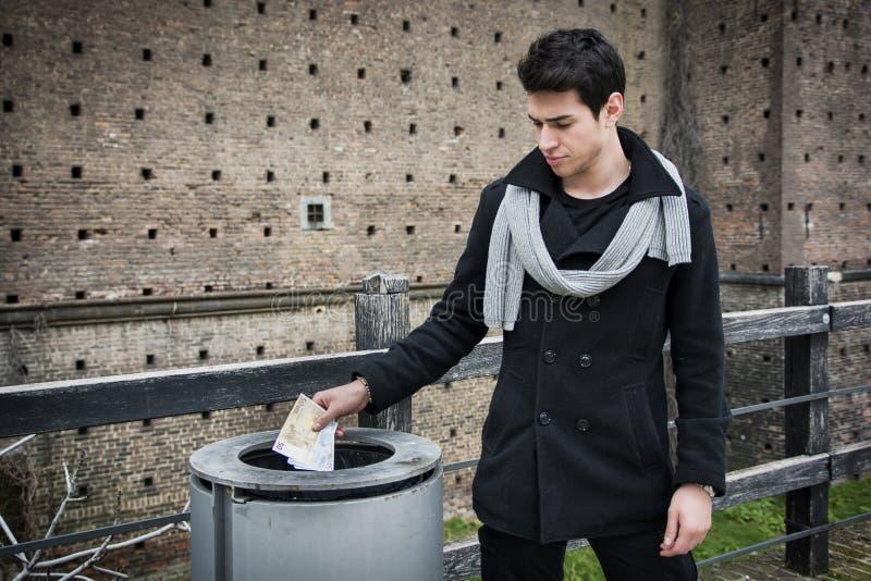 Argent de lancement de jeune homme beau dans la poubelle images stock