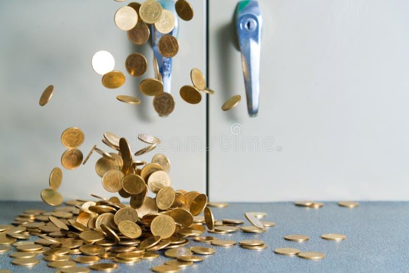 Argent en baisse de pièces d'or sur la table de bureau avec le coffret b de document image stock
