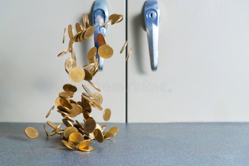 Argent en baisse de pièces d'or sur la table de bureau avec le coffret b de document image libre de droits