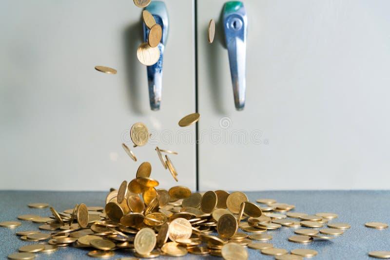 Argent en baisse de pièces d'or sur la table de bureau avec le coffret b de document photos stock