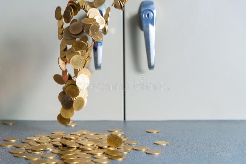 Argent en baisse de pièces d'or sur la table de bureau avec le coffret b de document photo libre de droits