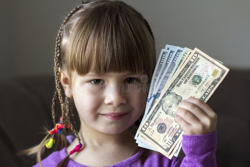 Argent, finances et concept de personnes - la petite fille de sourire avec le dollar encaissent l'argent photo stock