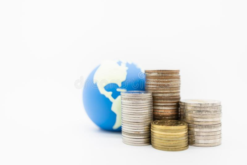 Argent global, finances et concept économisant Fermez-vous de la pile de pièces de monnaie devant la mini boule du monde avec le  image stock