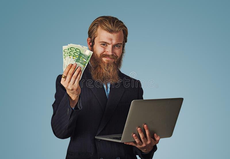 Argent liquide de sourire de factures d'ordinateur portable et d'argent de participation d'homme euro photos stock