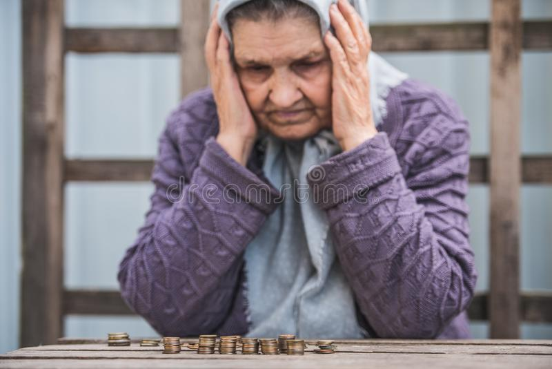 Argent, pièces de monnaie, retraité de grand-mère et le concept du minimum de subsistance - dame âgée triste regardant les pièces photo libre de droits