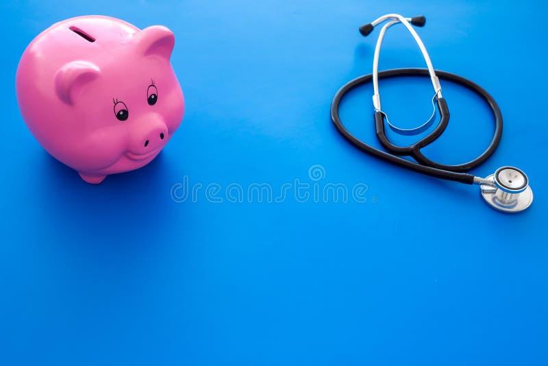 Argent pour le traitement Dépenses médicales Tirelire dans la forme du porc près du stéthoscope sur l'espace bleu de copie de fon photos stock