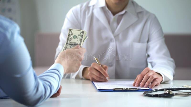 Argent se tenant patient, payant le docteur le traitement, clinique privée, assurance photographie stock libre de droits