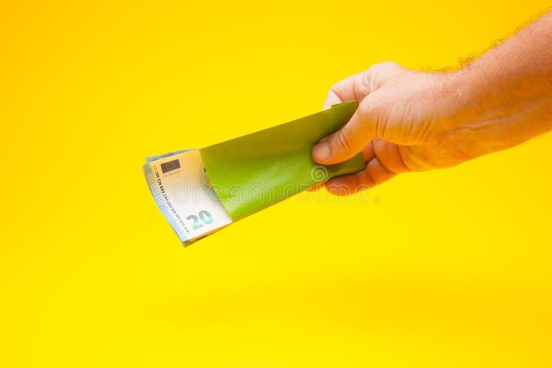 Argent sous enveloppe et dans la main d'une personne photo libre de droits