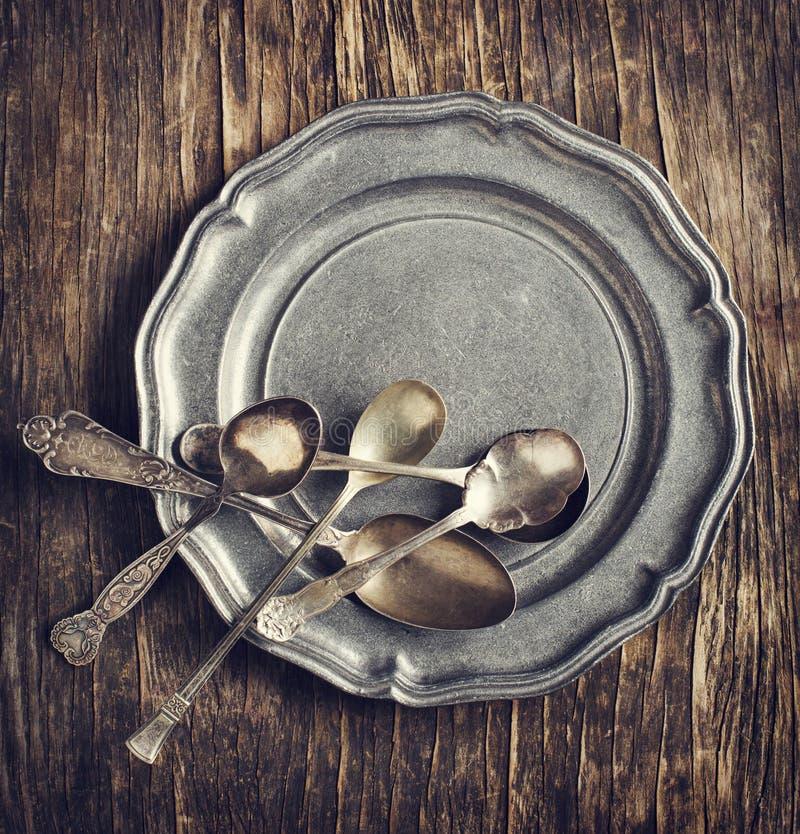 Argenteria d'annata su di piastra metallica rustico fotografia stock libera da diritti