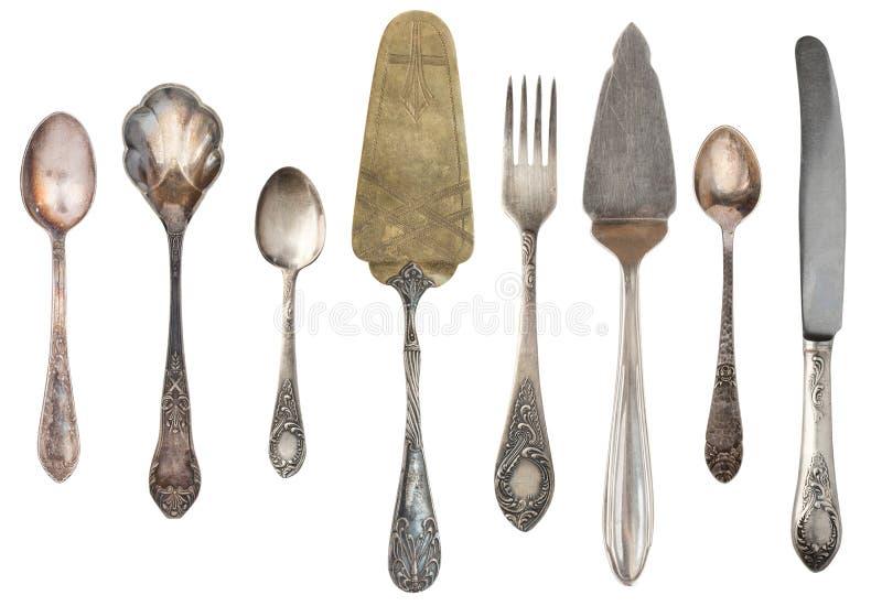 Argenterie antique de cru d'isolement sur le fond blanc Rétros cuillères, fourchettes, couteaux, pelles pour le gâteau photo libre de droits