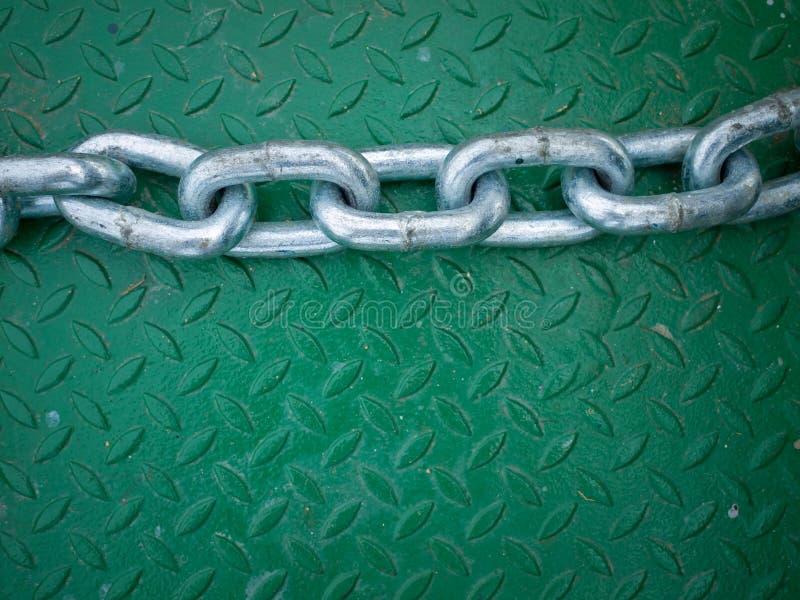 Argenti la catena sulla zolla di pavimento d'acciaio verde immagini stock