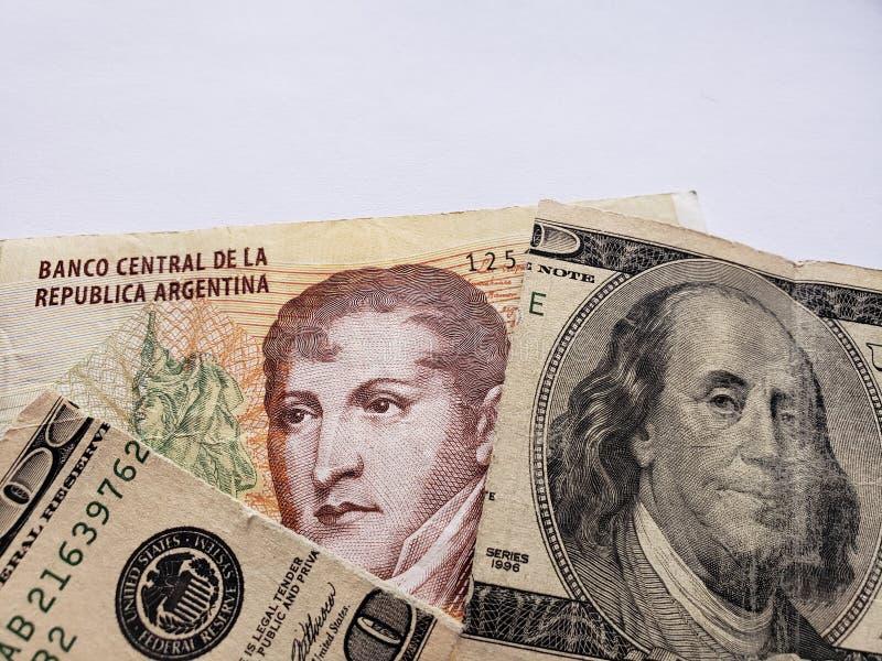 Argentijns bankbiljet van tien peso's en gebroken Amerikaans bankbiljet van 100 dollars