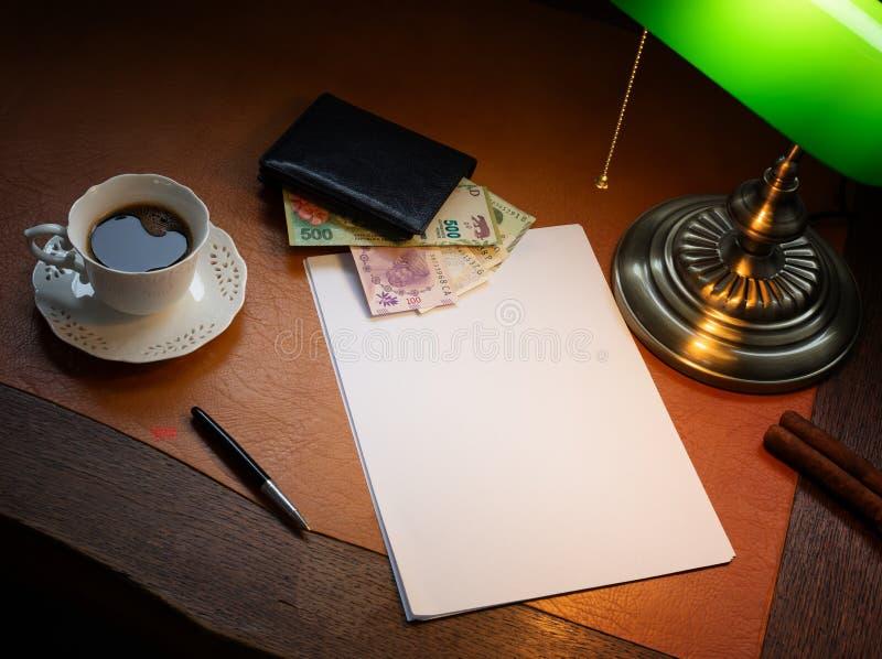 Argentijns geld op een modieus bureau met koffie en een lamp stock afbeelding