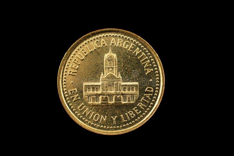 Or argentin pièce de monnaie de vingt-cinq centavos d'isolement sur le noir photos libres de droits