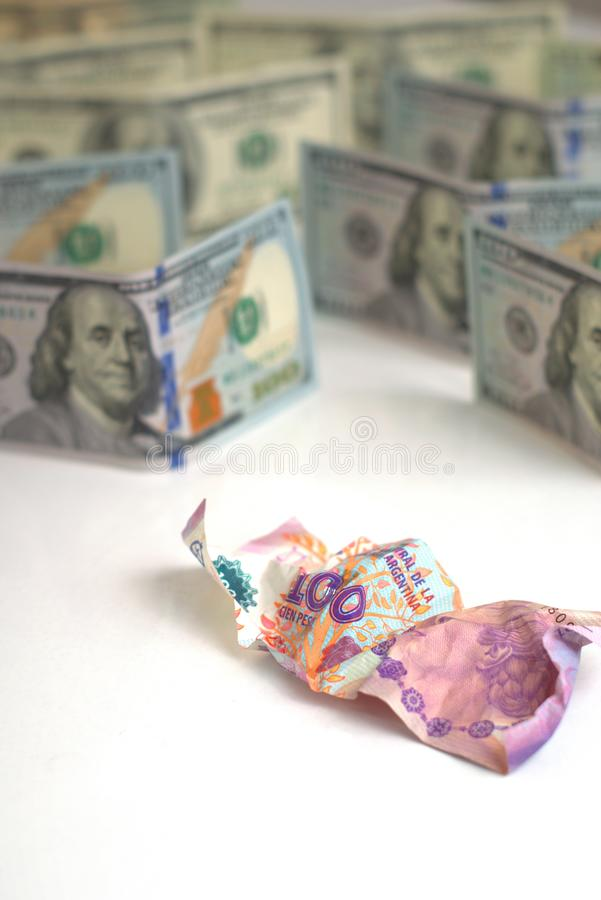 Argentina economic crisis and currency devaluation concept. Crumpled argentinian banknote and intact US banknotes. Argentina economic crisis and currency stock photography