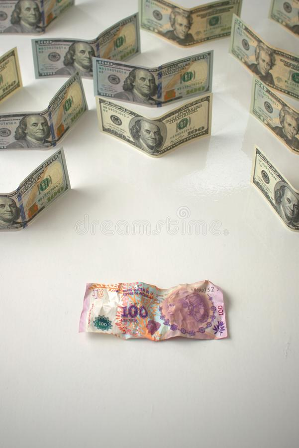 Argentina economic crisis and currency devaluation concept. Crumpled argentinian banknote and intact US banknotes. Argentina economic crisis and currency royalty free stock photo