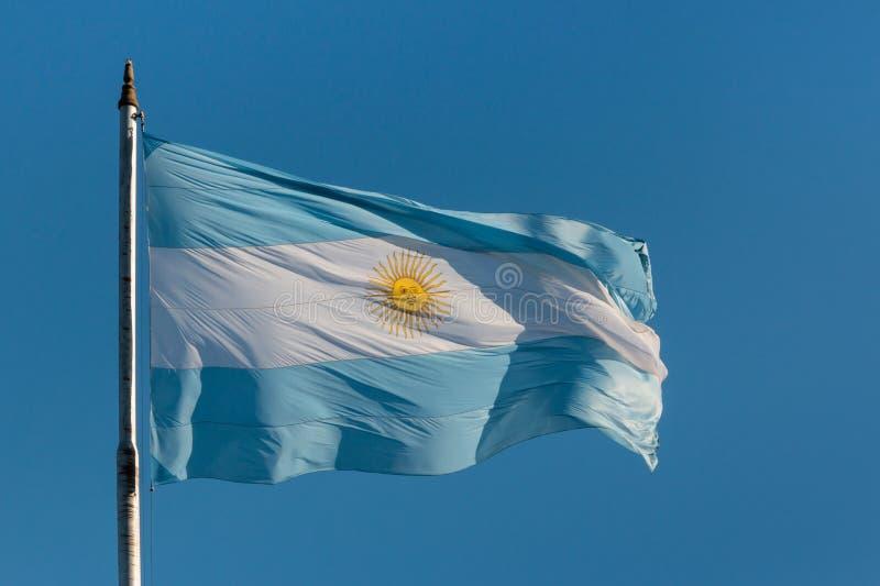Argentina flag flying on flagpole. Argentina flag flying against blue sky stock photography