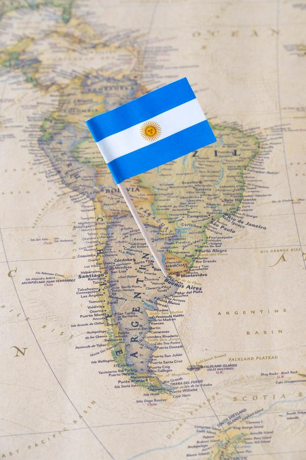 Argentina flag pin on a world map. Paper flag pin of Argentina, officially the Argentine Republic, on a world map. It is a federal republic located mostly in the stock photos