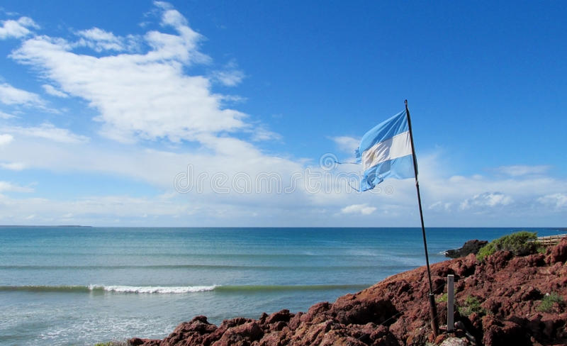 Argentina flag on a sea shore. Argentina flag on a sea, ocean shoreamong the red rocks. Deep blue sky and white clouds royalty free stock photography