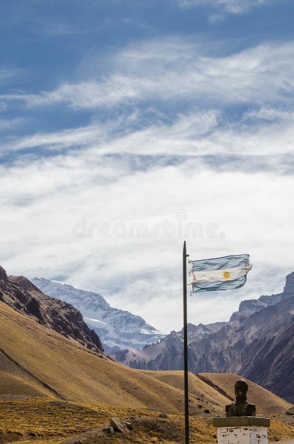 Argentina flag waving with historical bust and Aconcagua mountain behind. Argentina flag waving with historical bust of San Martin  and Aconcagua mountain stock photo