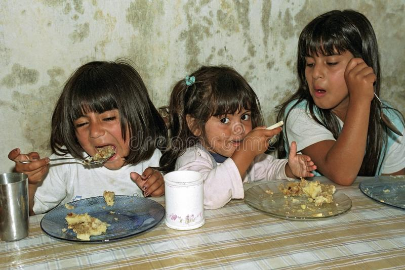 Poor hungry Argentinian girls eat in a soup kitchen stock photo