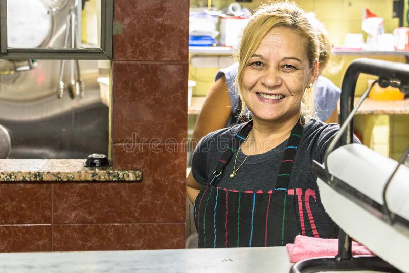 Argentinian female cook at El Trebol resto - bodegon in Buenos A. Buenos Aires, Argentina - March 20th, 2018: A female cook at the counter of the restaurant stock photography