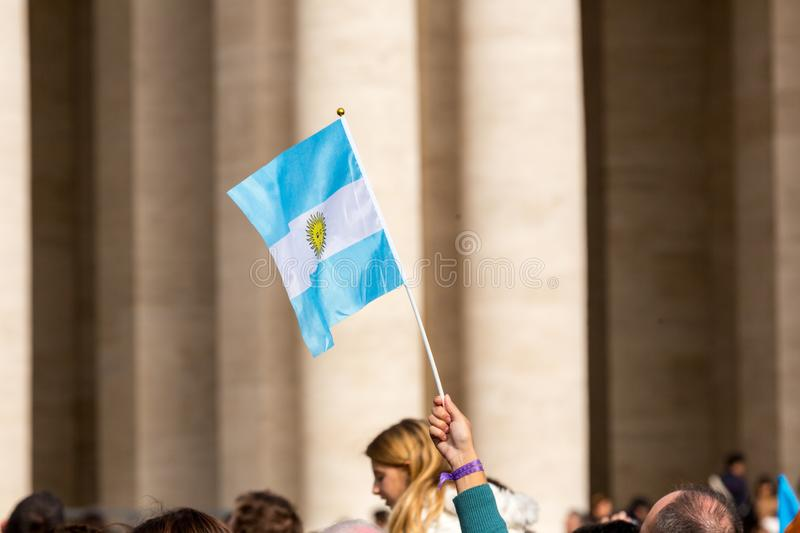 An Argentinian Flag. Vatican City, Vatican - February 22, 2015: A crowd gathers in St. Peter`s Square while someone waves a Argentinian flag in the sun royalty free stock image