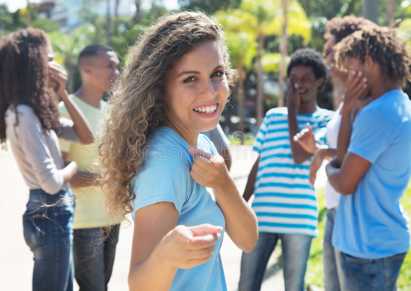 Argentinian girl with friends pointing at camera. In the city in the summer stock images