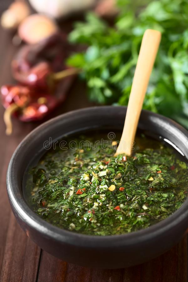 Argentinian Green Chimichurri Salsa. Raw homemade Argentinian green Chimichurri or Chimmichurri salsa or sauce made of parsley, garlic, oregano, hot pepper stock images