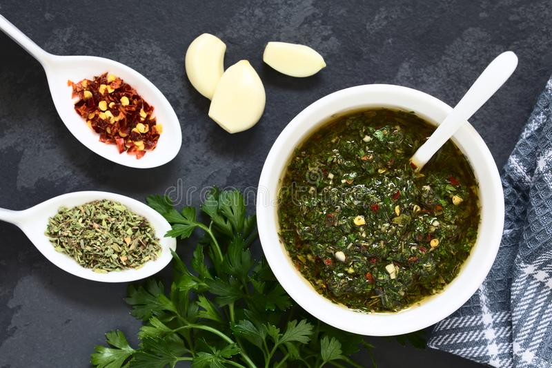 Argentinian Green Chimichurri Salsa. Raw homemade Argentinian green Chimichurri or Chimmichurri salsa or sauce made of parsley, garlic, oregano, hot pepper stock photo