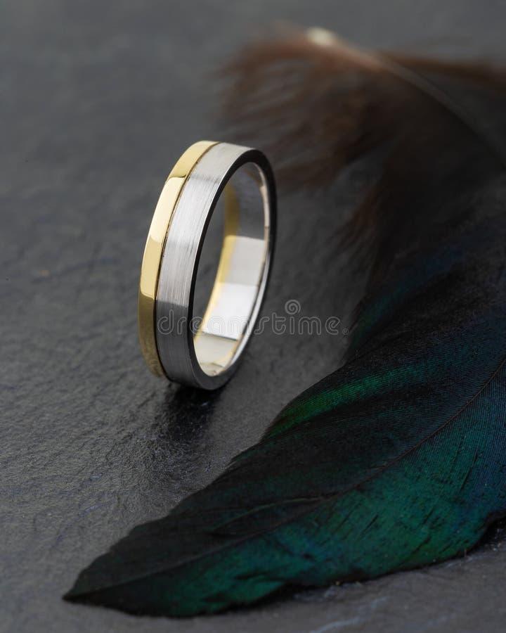 Argento ed anello combinato oro su fondo nero con feathe verde fotografia stock