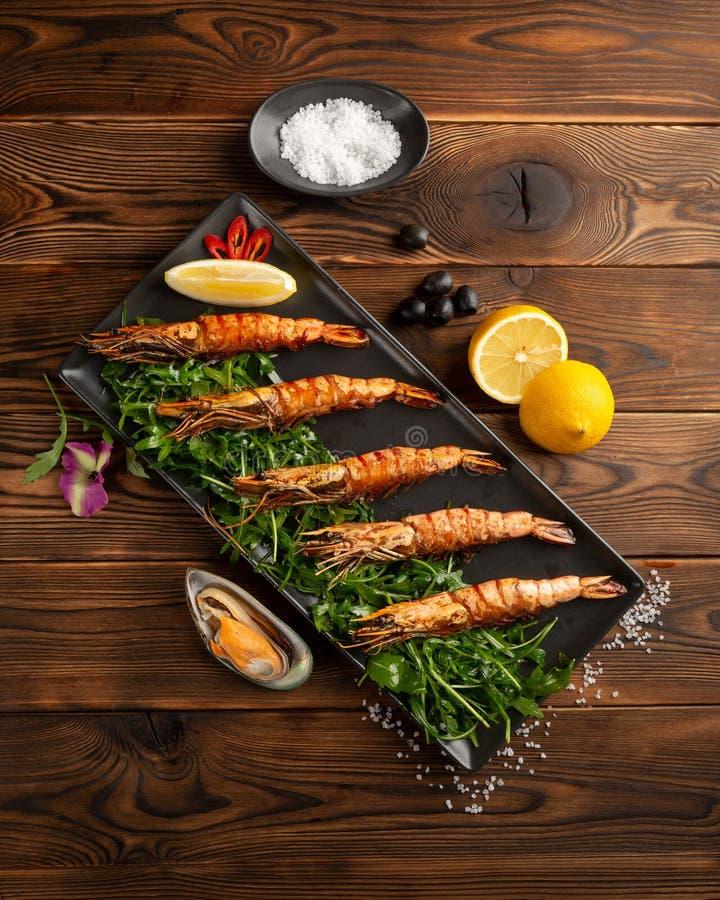 Argenty?skie piec na grillu krewetki w czarnym talerzu na drewnianym tle zdjęcia stock