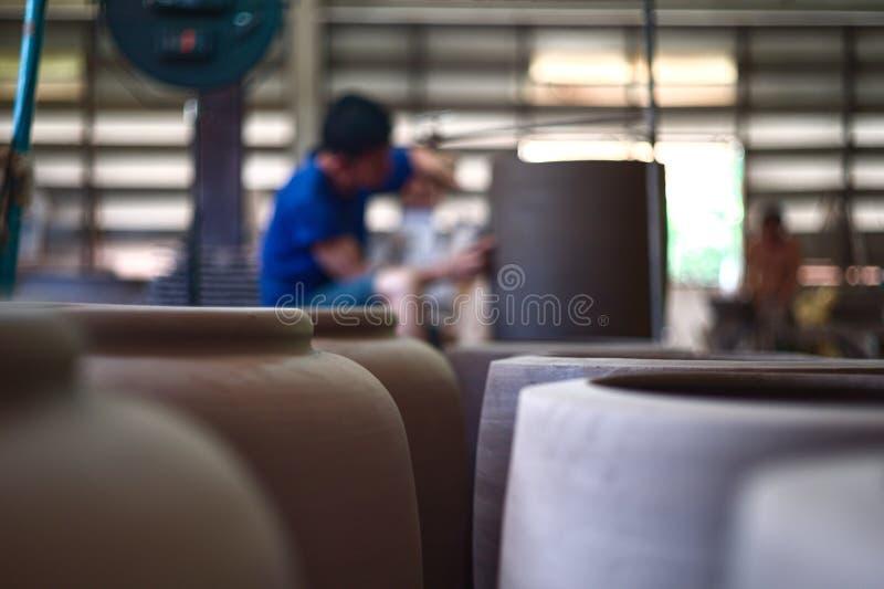 A argila range na linha de produção com o trabalhador borrado no fundo na fábrica da cerâmica Habilidade e produto feito a mão fotos de stock