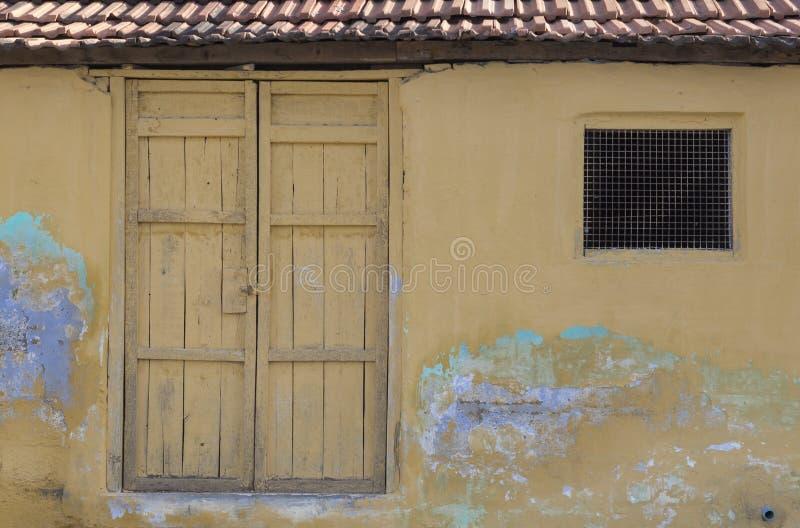 A argila velha telhou telhar a casa do estilo de Kerala com a pintura amarela vibrante e olhar antigo rústico a Índia recolhida foto de stock