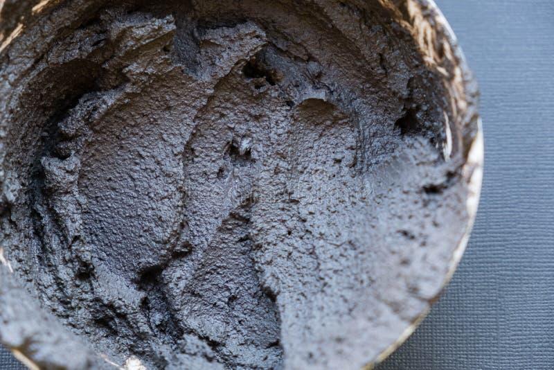 Argilla cosmetica vulcanica nera in una ciotola fine cosmetica di struttura dell'argilla su soluzione di fondo cosmetico dell'est fotografia stock