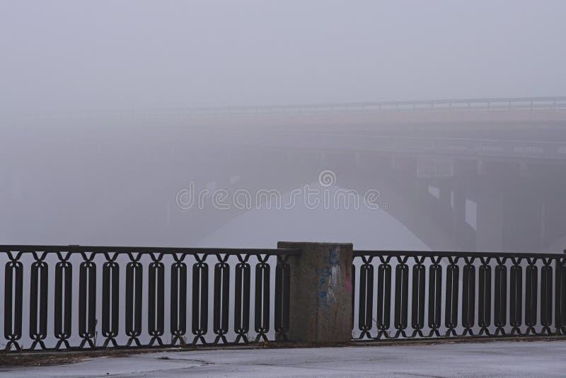 Argine lungo il fiume di Dnieper Ponte di pietra del sottopassaggio della metropolitana in nebbia ricca, fondo della foschia Vist fotografie stock