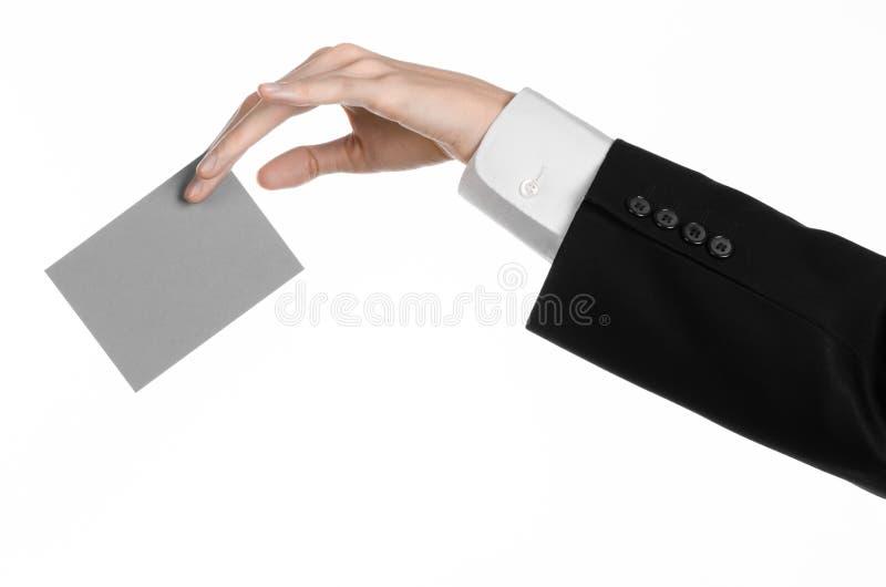 Argomento di pubblicità e di affari: Uomo in vestito nero che giudica un disponibile grigio della carta in bianco isolato su fond fotografie stock libere da diritti