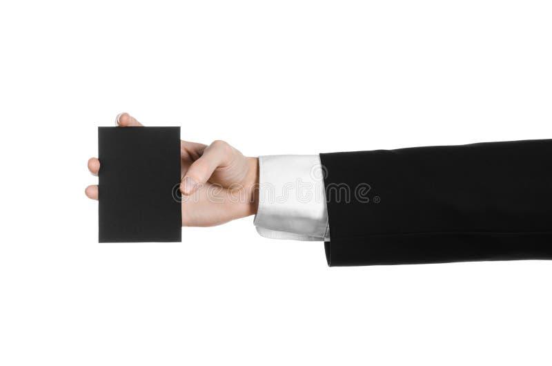 Argomento di pubblicità e di affari: Uomo in vestito nero che giudica un disponibile nero della carta in bianco isolato su fondo  fotografia stock