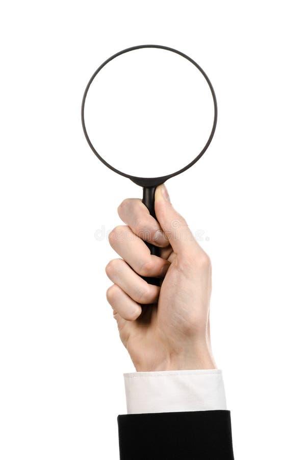 Argomento di ricerca di affari: l'uomo d'affari in un vestito nero che tiene una lente d'ingrandimento su un bianco ha isolato il fotografia stock libera da diritti