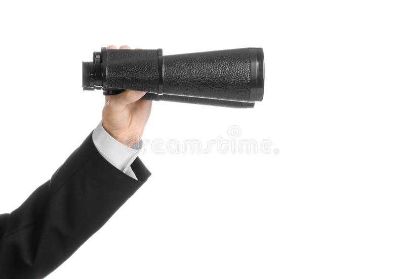 Argomento di ricerca e di affari: L'uomo in vestito nero che giudica binocolo nero disponibile su bianco ha isolato il fondo in s immagini stock