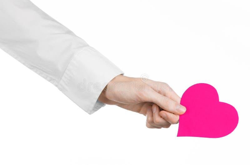 Argomento di salute e della malattia cardiaca: passi medico in una camicia bianca che giudica una carta sotto forma di cuore rosa fotografie stock