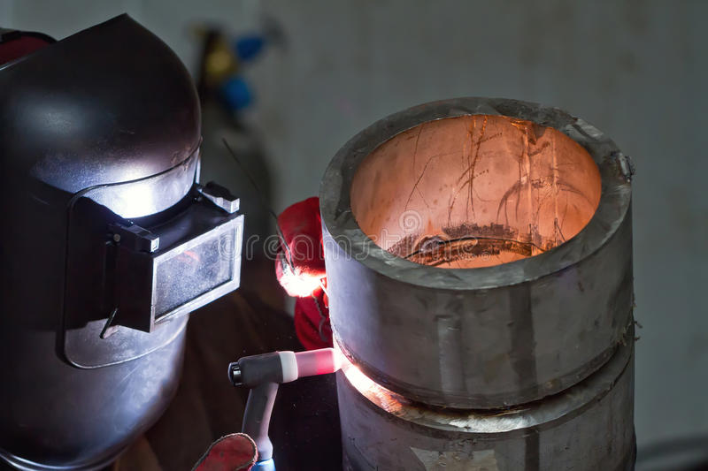 Argon arc welding of thick-walled stainless steel pipe. Welding control sample at 45 degrees from thick-walled stainless steel pipe by the method of argon arc royalty free stock photo