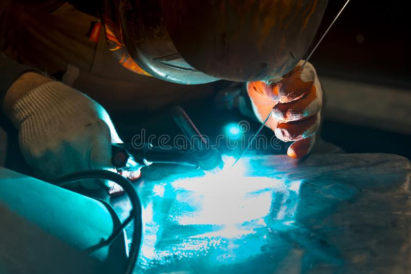 Argon-arc welding welder at the workplace welds the part. The welder ignites the arc and begins welding the aluminum canister with argon arc welding royalty free stock photo