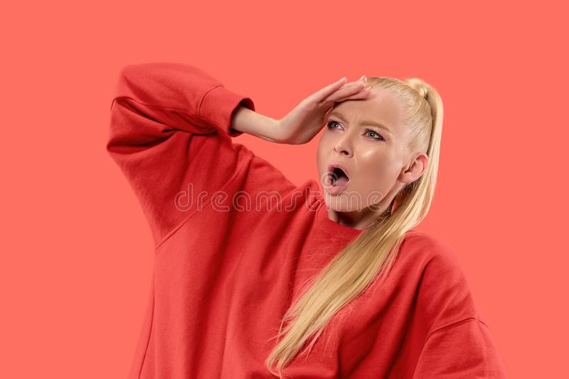 Beautiful female half-length portrait isolated on coral studio backgroud. The young emotional surprised woman. Argue, arguing concept. Beautiful female half stock images