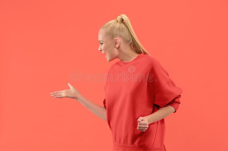 Beautiful female half-length portrait isolated on coral studio backgroud. The young emotional surprised woman. Argue, arguing concept. Beautiful female half royalty free stock photography