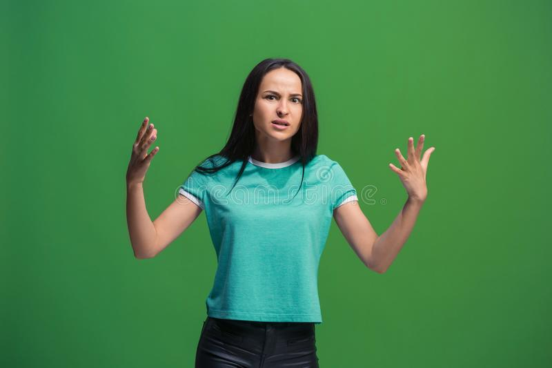 Beautiful female half-length portrait isolated on green studio backgroud. The young emotional surprised woman. Argue, arguing concept. Beautiful female half royalty free stock photo