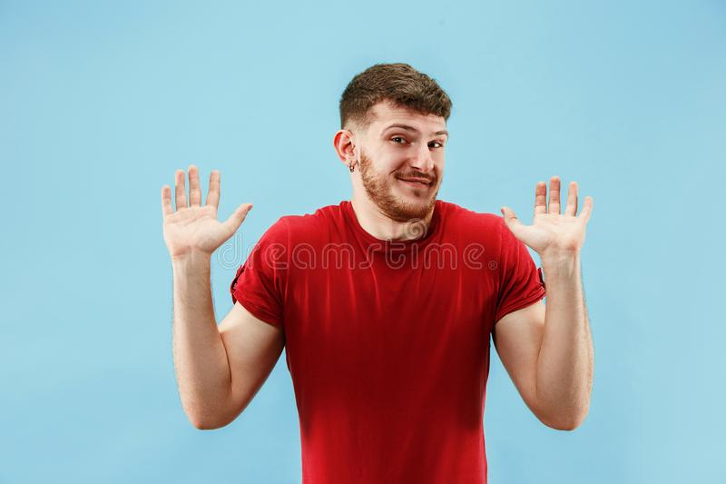 Beautiful male half-length portrait isolated on blue studio backgroud. The young emotional surprised man. Argue, arguing concept. Beautiful male half-length stock photography