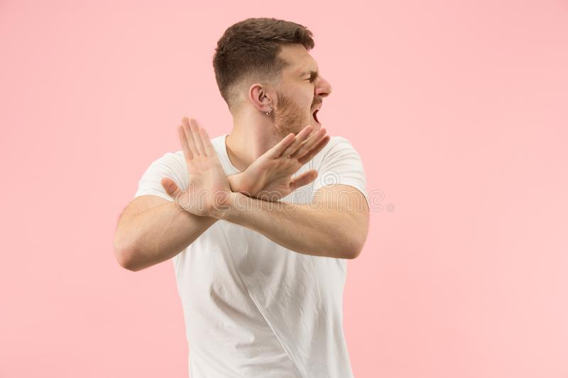 Beautiful male half-length portrait isolated on pink studio backgroud. The young emotional surprised man. Argue, arguing concept. Beautiful male half-length stock image